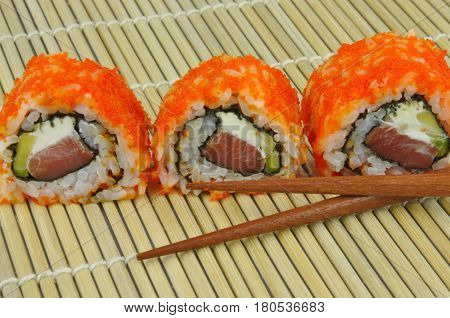 Sushi rolls with red masago roe, on bamboo mat with chopsticks