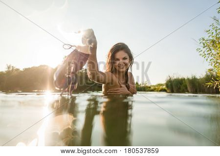Beautiful naked woman in lake at the summer sunny day