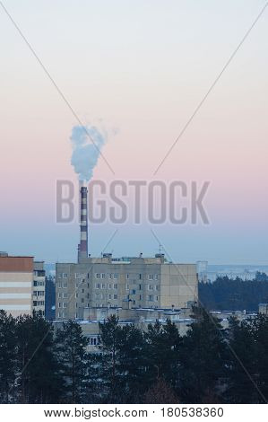 Fuming chimney over factory quarters in frosty air