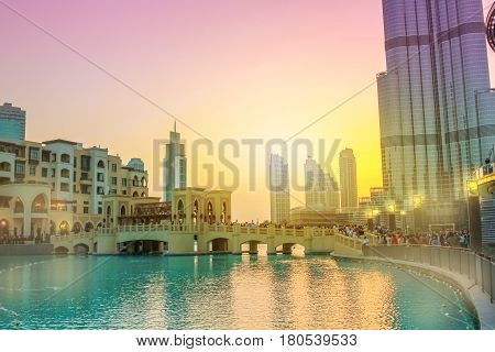 Scenic view of Burj Khalifa Lake, a pool where they dance the Dubai Fountain. On background, the Souk Al Bahar and Burj Khalifa at dusk in Dubai Downtown District, United Arab Emirates.
