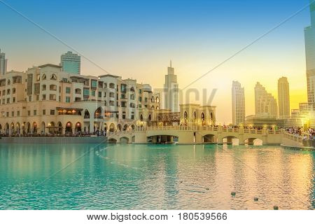 Scenic view of Burj Khalifa Lake, a pool where they dance the Dubai Fountain. On background, the bridge that connects the Dubai Mall to Souk Al Bahar. People crowd around the shopping area at sunset.