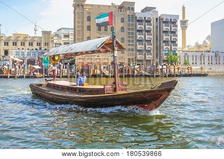 Dubai, United Arab Emirates - May 3, 2013: a traditional dhow ferry along Dubai Creek. The Creek divides the city into two main sections: Deira and Bur Dubai, a historic district in Dubai.