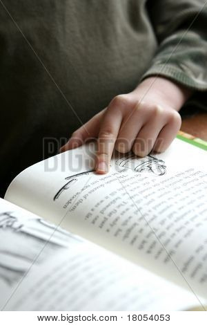 Seeking knowledge : A finger of a child pointing to a word in a book as he reads