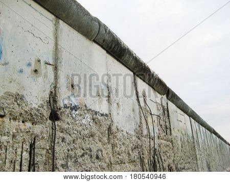 BERLIN, GERMANY - JULY 20, 2016: Berlin Wall detail in downtown Berlin, Germany. Historical symbol separating East and West Berlin after Second World War and Cold War on cloudy dark day