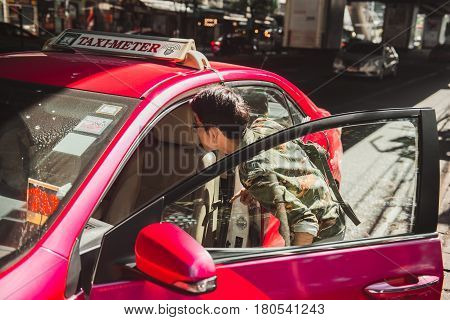 BANGKOK THAILAND - JANUARY 22: Street scene in downtown Bangkok of a man trying to catch a taxi on January 22 2017 in Bangkok.