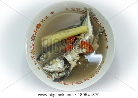Fish soup with sliced fish,chilli and lemon grass  on white background.The health benefits of fish soup with lemon grass include relief from stomachdisorders,insomnia,respiratorydisorders,fever,aches,infections,rheumatism & edema.