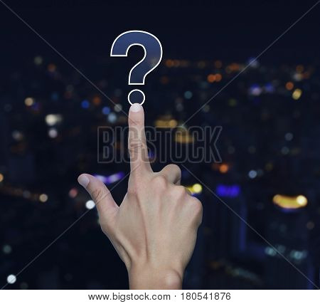 Hand pressing question mark sign icon over blur light city tower background Customer support concept