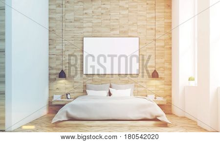 Front view of a bedroom with light wooden walls a double bed with gray bedding and a large horizontal poster hanging above it. 3d rendering mock up toned image
