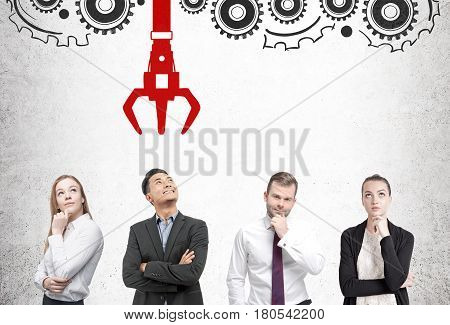 Front view of businesspeople standing near a concrete wall with a conveyor belt and a grappling hook. Concept of HR.