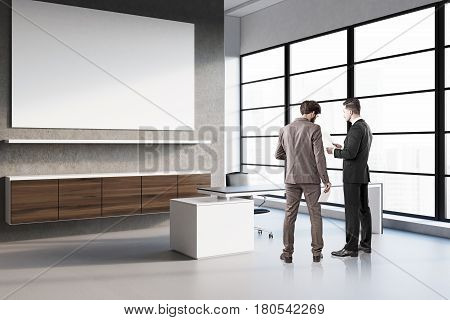 Two businessmen are standing in a CEO office with a large poster hanging on a gray wall and discussing work issues. 3d rendering mock up
