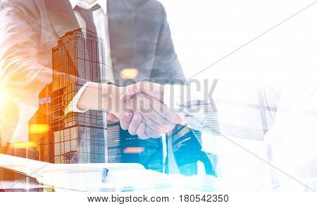 Close up of two business partners shaking hands at a table. There is a sunny city panorama in the foreground. Toned image double exposure.