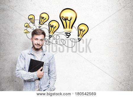 Portrait of a bearded young man wearing a jeans shirt and standing with his notebook near a concrete wall with many yellow light bulbs connected with a wire.