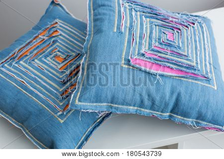 textile two blue pillows on a white background, close up on the pillows decorated with stitching and designer decors in the form of a labyrinth cut in the fabric through which visible colored lining.