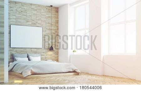 Side view of a bedroom with light wooden walls a double bed with gray bedding and a large horizontal poster hanging above it. 3d rendering mock up toned image