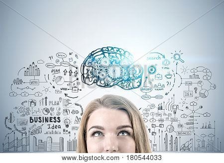 Close up of a head of a blond woman against a gray wall with a brain sketch gears and a business plan drawn on it. Toned image.
