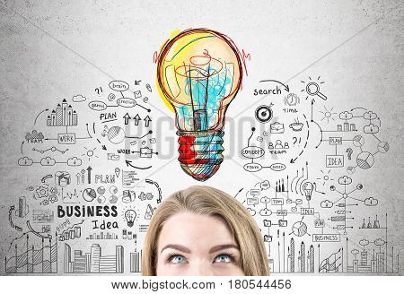 Close up of a head of a woman with blond hair standing near a concrete wall with a business idea sketch drawn on it.