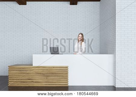 Portrait of a blond receptionist standing at a white and wooden counter with a gray laptop on it. 3d rendering.