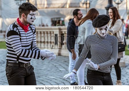 TIMISOARA ROMANIA - MARCH 31 2017: Pantomime couple with painted face present on the street inside the CheckART Carnival organized by the City Hall Timisoara. Union Square.