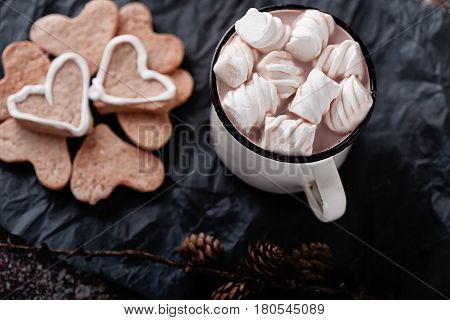 A cup of hot cocoa marshmallows and cookies and heart marshmallows cinnamon sticks