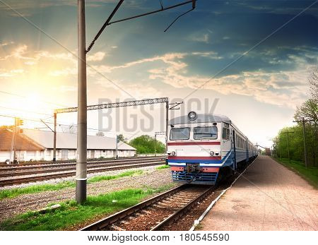 Modern train at a railway station in the rays of the sun
