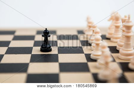 Chess game with black pawn ready to attack the white pawns on a wooden chessboard