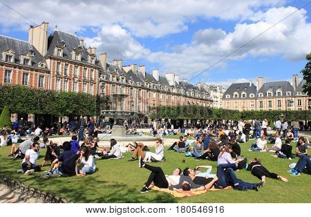 PARIS FRANCE - MAY 24 2015: People relaxing on green lawns of the famous Place des Vosges - the oldest planned square in Paris located in Marais district on May 24 2015 in Paris