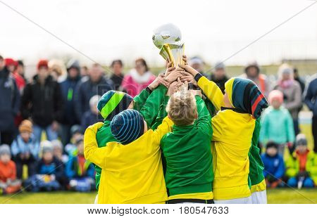 Young Soccer Players Holding Trophy. Boys Celebrating Soccer Football Championship. Winning Youth Team of Sport Tournament for Kids Children. Children as Sports Champions