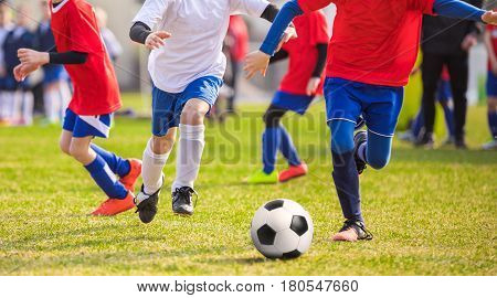 Junior Football Players Playing A Match. Footballers Kicking Football Match Game. Running Soccer Football Players