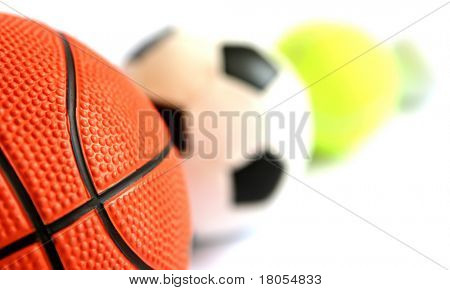 One shape, different colours and designs. A basketball, a football, a tennisball and a golfball - shallow depth of field
