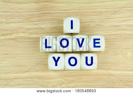 Blue Alphabets on White Cube Blocks say I LOVE YOU on the Wooden Surface Background