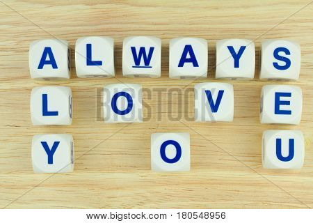 Blue Alphabets on White Cube Blocks say ALWAYS LOVE YOU on the Wooden Surface Background