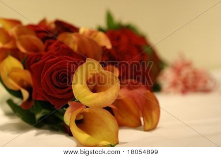 An arrangement of a wedding hand bouquet consisting of red roses and orange tulips