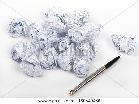 crumpled paper and pen on white background closeup