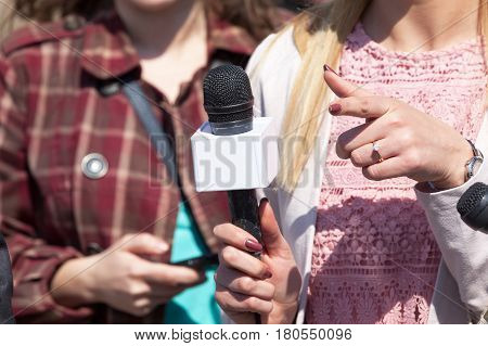 Female reporter holding microphone conducting media interview