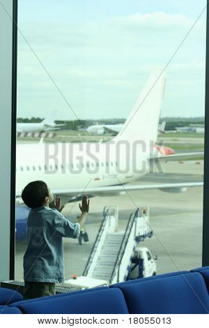 I'd like to fly like a plane. A little boy stands in awe at the sight of plane parked outside the viewing gallery