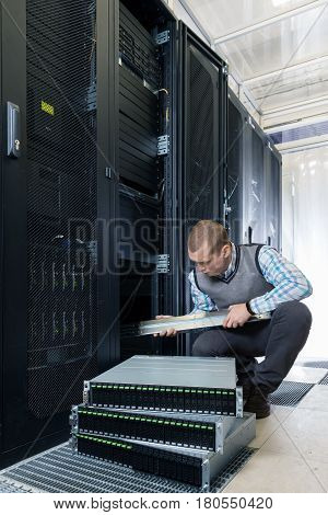 IT Engineer installs enclosure with hard disk drive in the storage system in the rack in datacenter