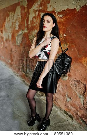 Young Goth Girl On Black Leather Skirt With Backpack Posed Against Grunge Wall.
