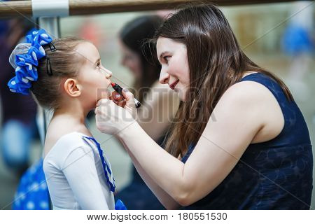 Mother makes make-up her daughter. Mother putting lipstick on her daughter on mirror background. Mom helping little daughter to use lipstick before a dance performance. Shallow depth of field. Selective focus.