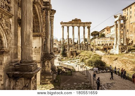 ROME, ITALY - MAY 15, 2014: Arch of Emperor Septimius Severus and Temple of Saturn in the distance at the Roman Forum.