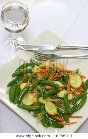 A plate of healthy stir fry vegetables and a glass of water.