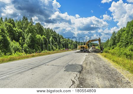 PERM KRAI RUSSIA - JULY 12 2016: The repair of the road using an excavator on a summer day