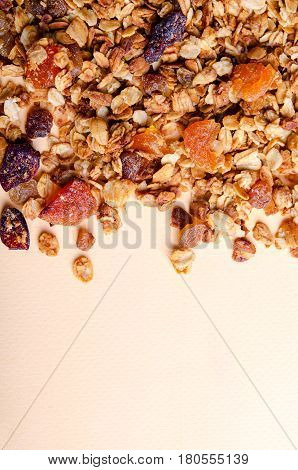 Homemade granola with honey, oatmeal, nuts, raisin, cranberry and dried apricots for background, vertical, copy space