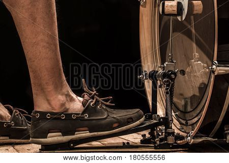 percussion instrument, bass drum with pedal on wooden Board with black background, musical concept, men's foot