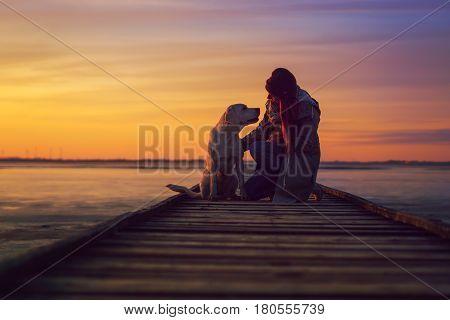 labrador retriever dog and woman on beach by sunset