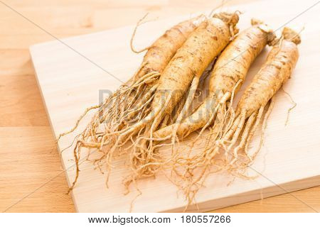 Fresh ginseng over wooden background