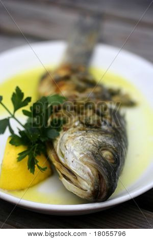 A whole grilled seabass on white plate served with caper dressing and a slice of lemon