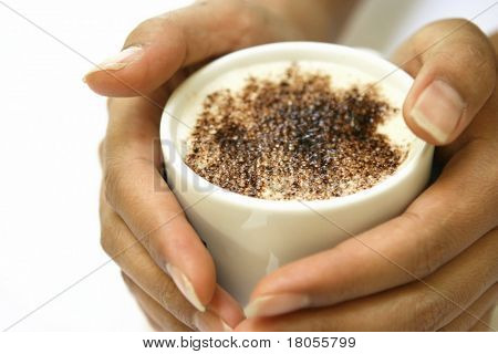 A pair of lady's hand gently holding a mug of hot cappucino coffee with chocolate sprinkle on top