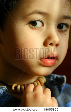 A little boy toying with his edible cherios necklace, unsure if he should eat it or leave it.