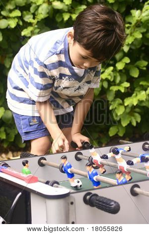 A young boy competing with his friend at mini table football in the garden