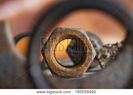 Macro composition of a rusty nut amongst other scrap metal